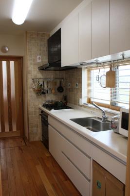 キッチンは玄関から直接入れます。階段下のスペースに食器棚と収納庫を組み込みました。床はケヤキの無垢板に低温水式暖房仕様となっています
